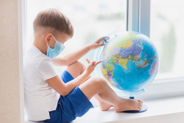 A criança mascarada fica em casa em quarentena. a criança está examinando o globo enquanto está sentada no parapeito da janela
