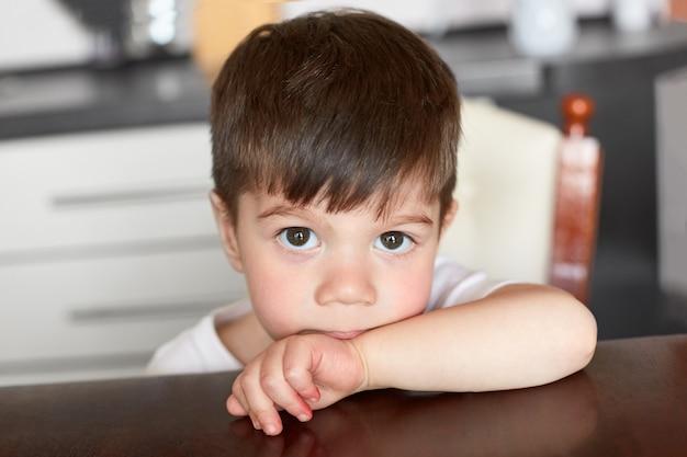 A criança masculina pequena de olhos escuros espreita sobre a borda da mesa, espera o jantar, posa contra o fundo desfocado da cozinha. filho pequeno atraente com olhos encantadores, cabelos pretos