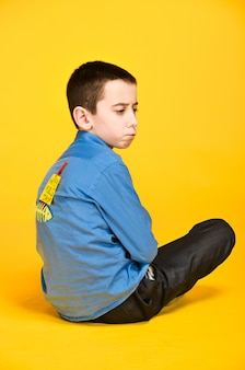 A criança medita envolvida na inscrição de ioga no dia do tolo