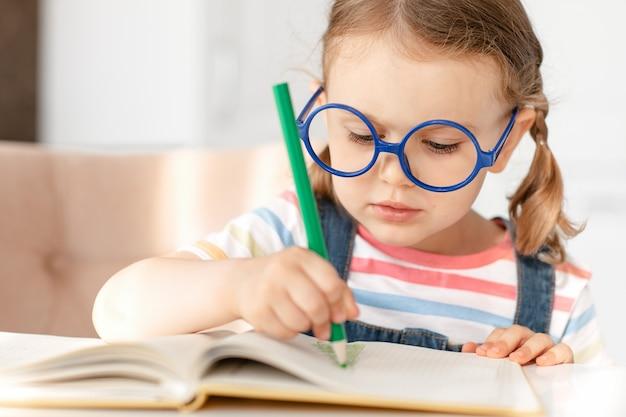 A criança menina aprende a escrever, a fazer o dever de casa, a sentar-se à mesa sozinha a fazer anotações a desenhar a lápis de cor