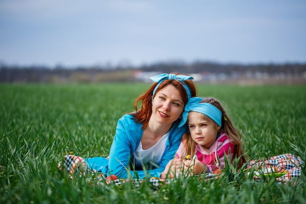 A criança menina e a mãe mulher deitam-se na colcha, grama verde no campo, clima ensolarado de primavera, sorriso e alegria da criança, céu azul com nuvens