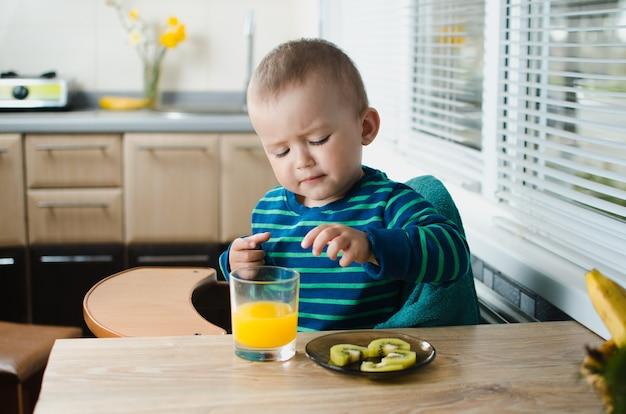A criança na cozinha com o suco de laranja e o kiwi, saudável, fofa e linda