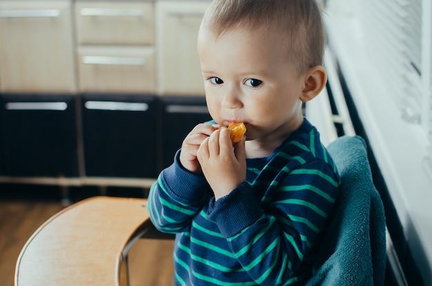 A criança na cozinha comendo um delicioso e suculento mandarim, uma vida saudável