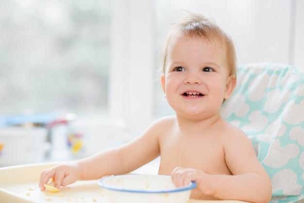 A criança na cozinha comeu mingau