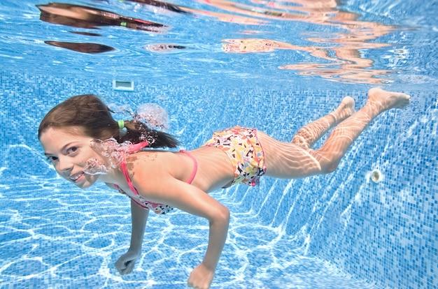 A criança nada debaixo d'água na piscina, a menina ativa mergulha e se diverte debaixo d'água, faz exercícios infantis e pratica esportes nas férias em família