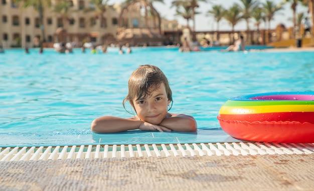A criança nada e mergulha na piscina. foco seletivo.