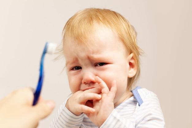 A criança não quer escovar os dentes e está infeliz.