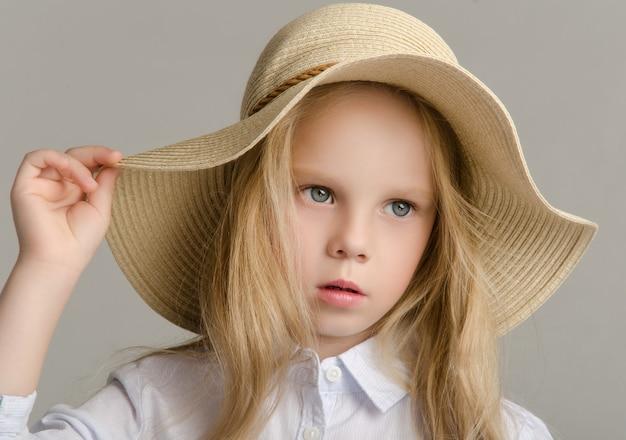 A criança no estúdio posando com roupas da moda