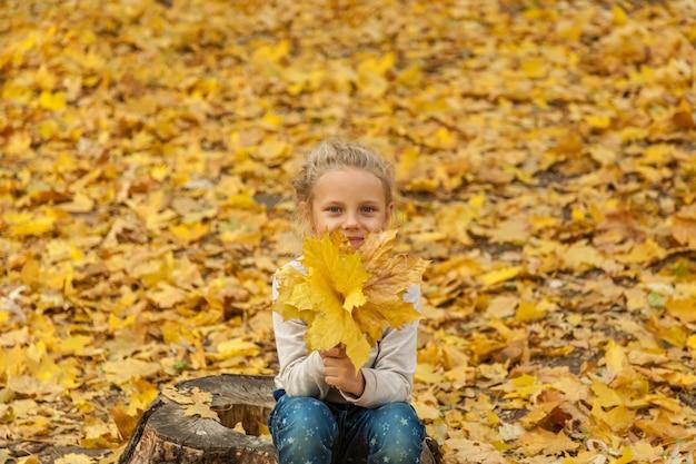 A criança no parque. uma menina sentada no toco no parque de outono com um monte de folhas caídas