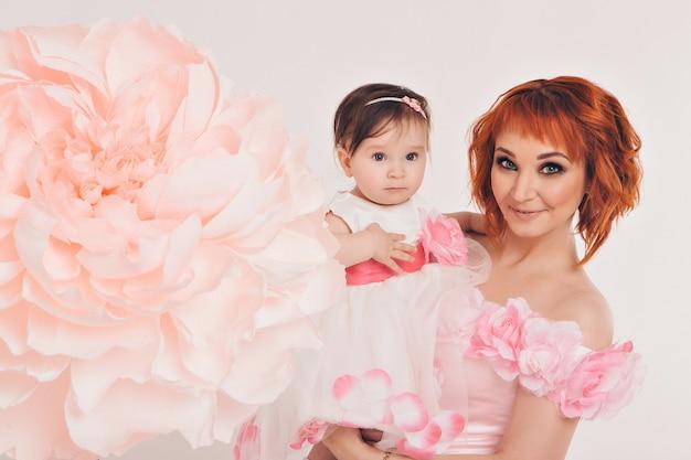 A criança nos braços de sua mãe em um vestido rosa de flores.