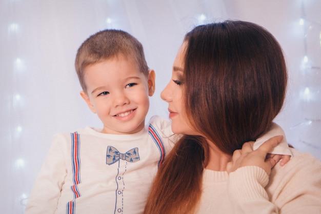 A criança nos braços de sua mãe no fundo de luzes e elementos decorativos