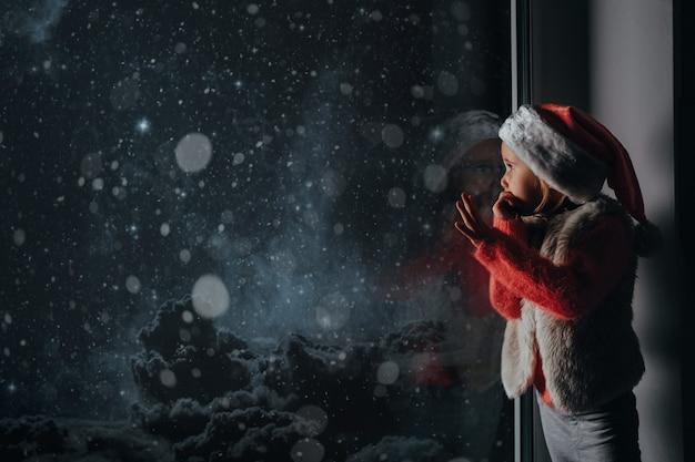 A criança olha pela janela no dia de natal