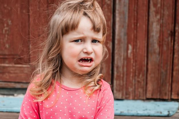 A criança órfã dos sem-teto chora pelas ruínas. terrorismo, guerra.