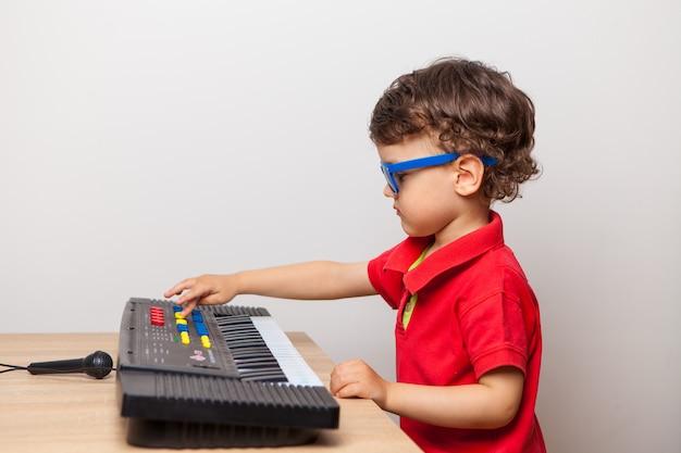 A criança organiza um concerto em casa para os pais que tocam o sintetizador.
