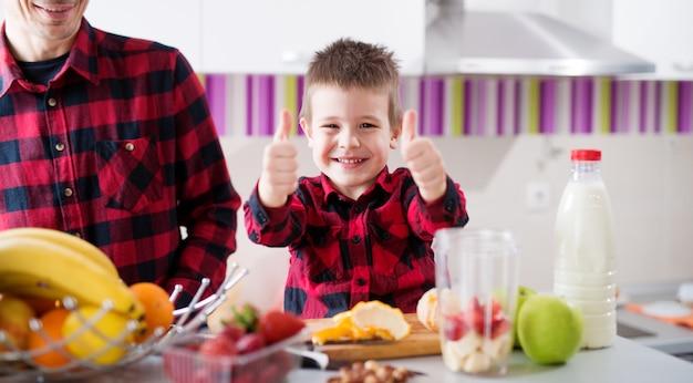 A criança orgulhosa feliz nova está aparecendo polegares ao preparar o lanche saudável da fruta com seu pai que senta-se no balcão da cozinha brilhante.