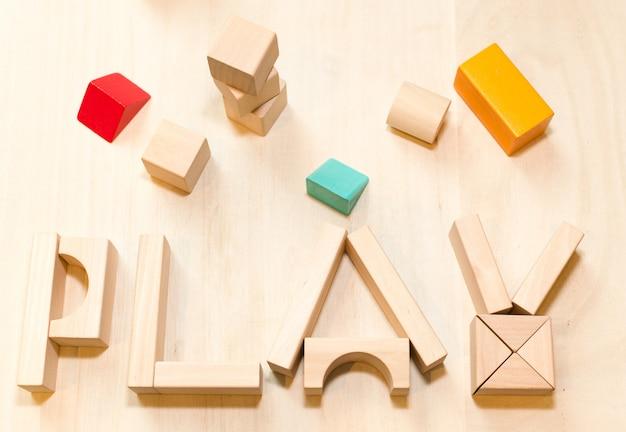 A criança ou o bebê jogam o grupo, blocos de madeira do brinquedo. jardim de infância ou fundo pré-escolar.