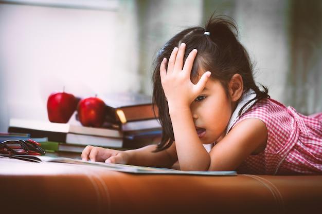 A criança pequena asiática está entediada por ler um livro. tom de cor vintage