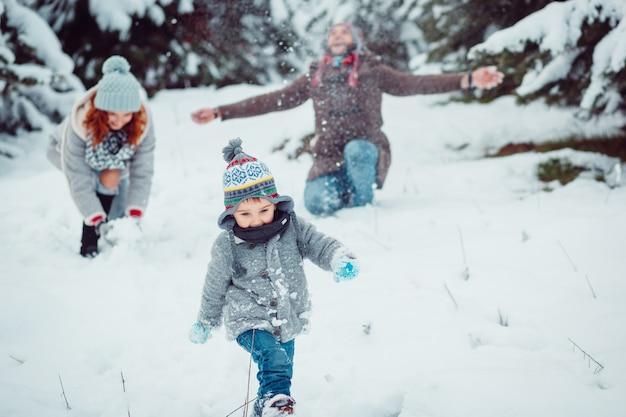 A criança pequena correndo ao longo da neve