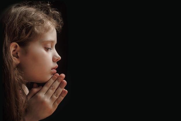 A criança pequena dobrou sua mão com rezar no fundo preto.