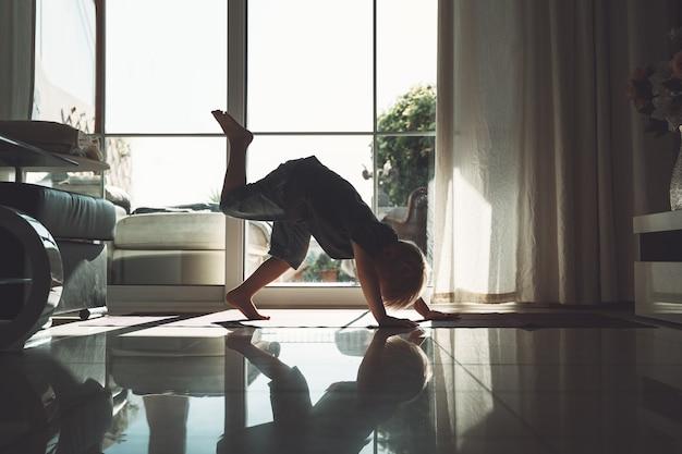 A criança pequena iogue está praticando ioga dentro de casa, a silhueta da criança fofa na pose de cachorro voltado para baixo