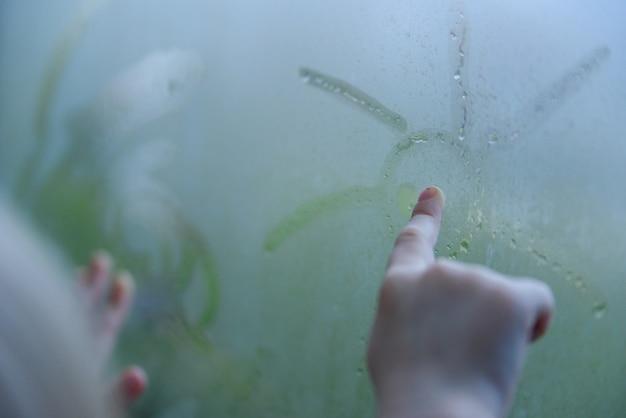 A criança pequena perto da janela. garoto em um dia chuvoso desenha o sol na janela embaçada.