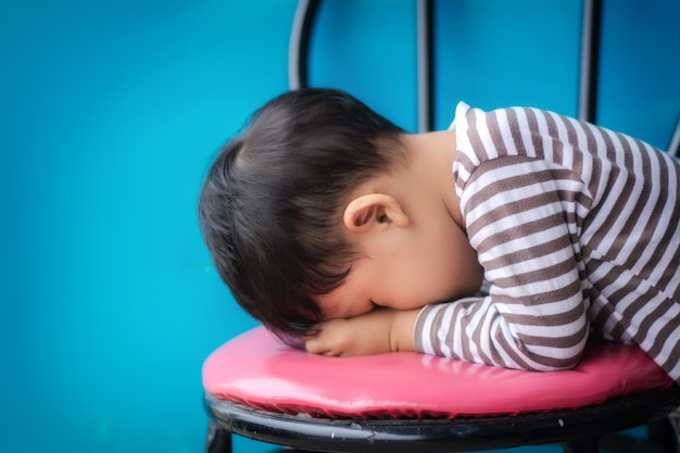 A criança pequena triste na cadeira contra o fundo azul e pensa da mãe.