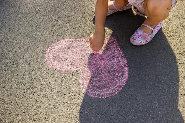 A criança pinta giz no coração de asfalto. foco seletivo.