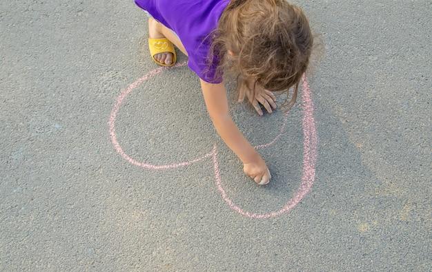 A criança pinta giz no coração do asfalto