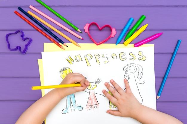 A criança pinta um esboço da família