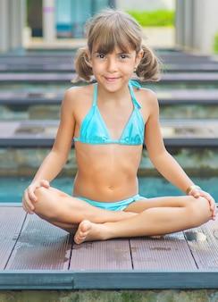 A criança pratica ioga no verão