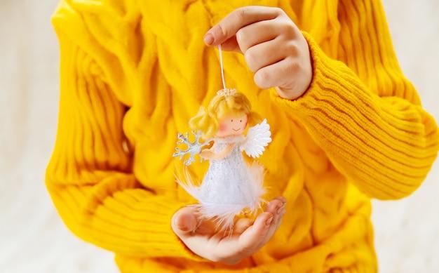 A criança prende uma decoração e presentes do natal em um fundo branco. foco seletivo.