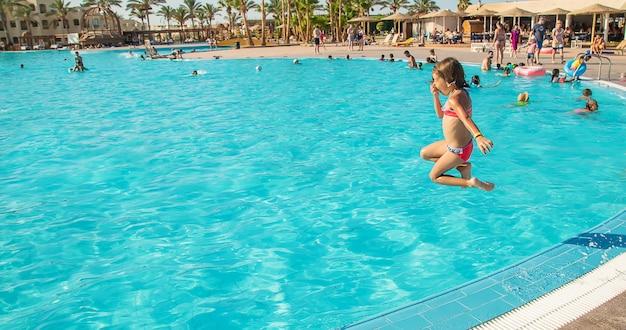 A criança pula na piscina. foco seletivo.