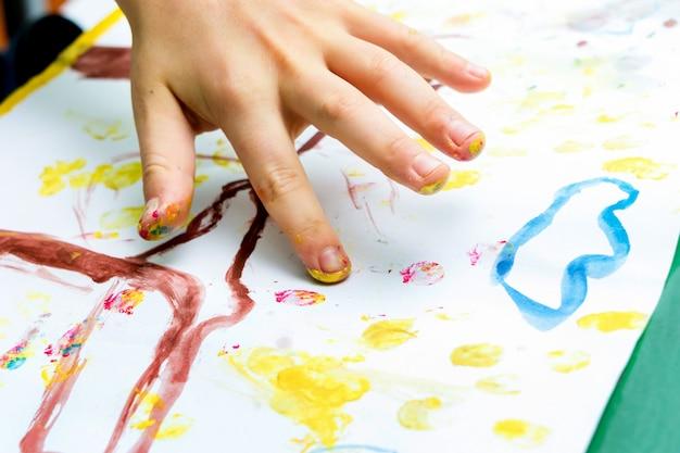 A criança realiza um desenho em papel com os dedos