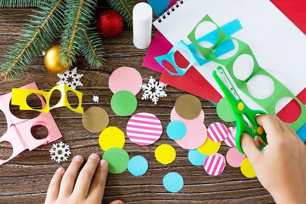 A criança recorta os detalhes cartão de saudação da árvore de natal feito à mão