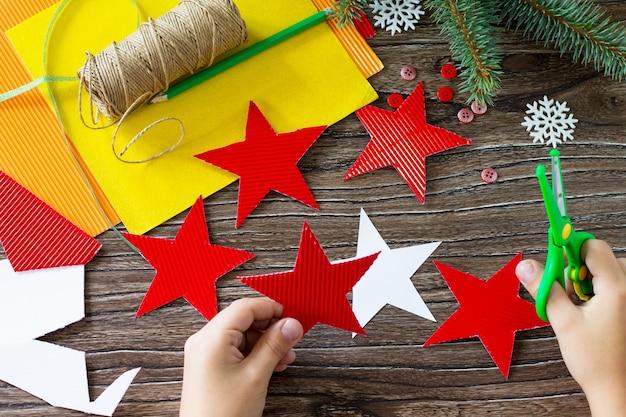 A criança recorta os detalhes presente estrela dos brinquedos da árvore de natal projeto de criatividade infantil