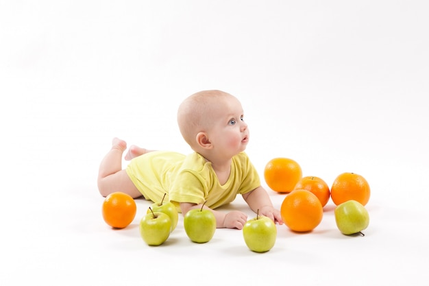 A criança saudável de sorriso bonito encontra-se em um fundo branco entre frut