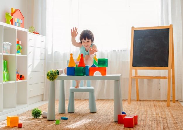 A criança se entrega a brincar na sala. pré-escolar, jardim de infância, 3 anos