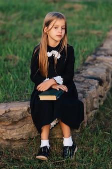 A criança se senta em um banco de pedra com um livro nas mãos e olha para longe.