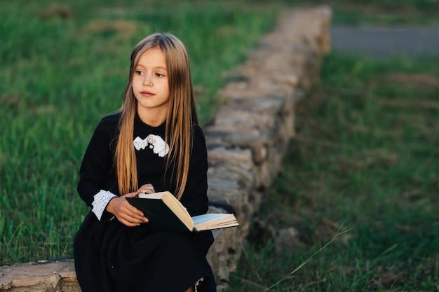 A criança se senta em um banco de pedra, segura um livro nas mãos e olha para longe.