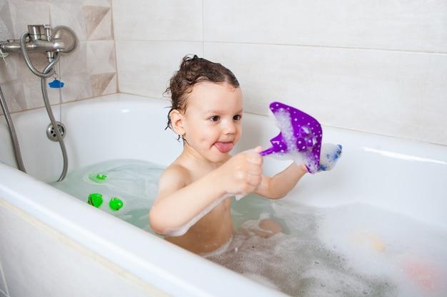 A criança se senta em um banho com água e brinca com peixe. higiene. mergulhar de uma maneira divertida.