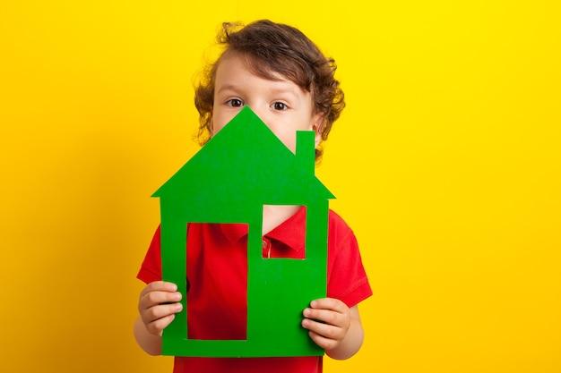 A criança segura a casa verde sobre um fundo amarelo. foto conceitual. o menino está escondido atrás da casa.