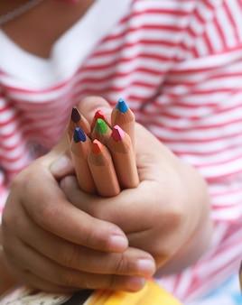 A criança segura lápis de cor na pequena mão