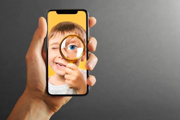 A criança segura o telefone na mão