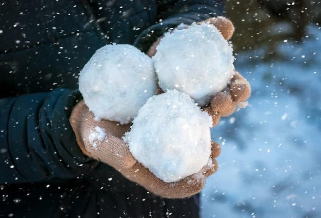 A criança segura três bolas de neve nas mãos