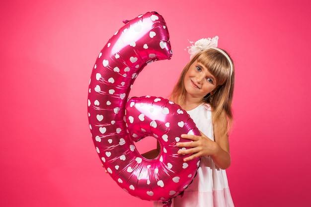 A criança segura um balão no estilo do número 6