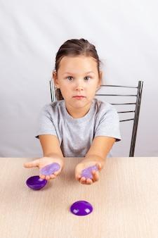 A criança segura um brinquedo de gosma nas mãos e se senta à mesa, desenvolvendo habilidades motoras finas.