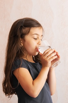 A criança segura um copo d'água nas mãos. foco seletivo. pessoas