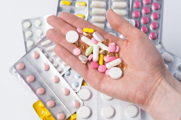A criança segura um garfo na mão, brinca com comprimidos multicoloridos. o conceito dos perigos do uso de comprimidos por crianças.