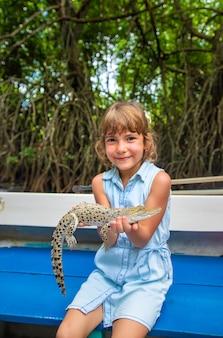 A criança segura um pequeno crocodilo nas mãos. foco seletivo. natureza.