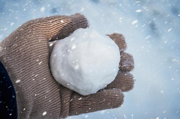 A criança segura uma bola de neve nas mãos durante uma nevasca